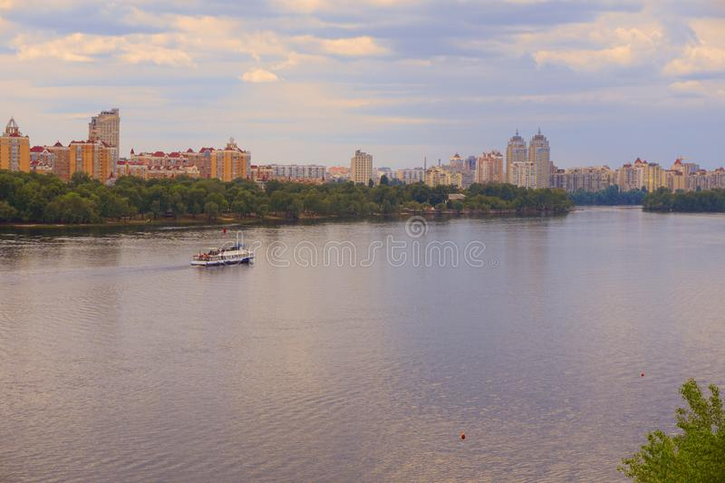 Yacht ship, boat goes on surface of the Dnieper Dnipro, Dnepr river against the background of city skyscrapers stock image