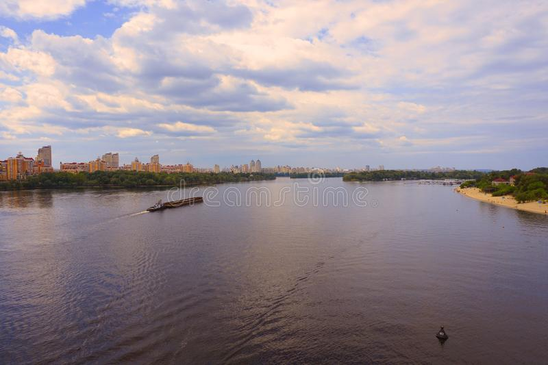 Yacht ship, boat goes on surface of the Dnieper Dnipro, Dnepr river against the background of city skyscrapers stock photo