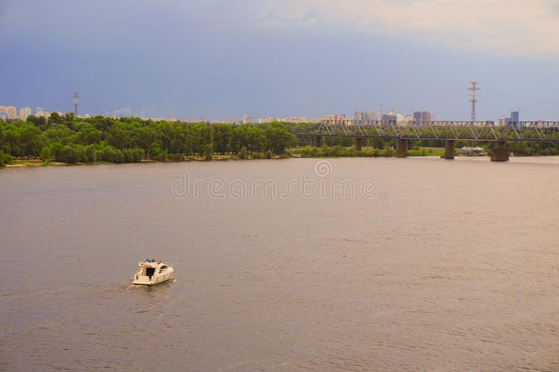 Yacht ship, boat goes on surface of the Dnieper Dnipro, Dnepr river against the background of city skyscrapers royalty free stock image