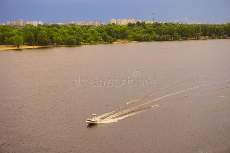 Yacht ship, boat goes on surface of the Dnieper Dnipro, Dnepr river against the background of city skyscrapers stock photography
