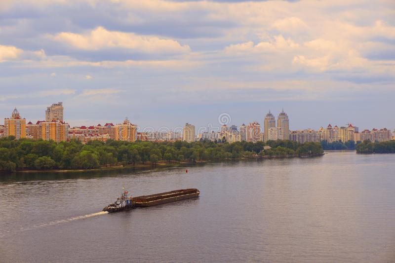 Yacht ship, boat goes on surface of the Dnieper Dnipro, Dnepr river against the background of city skyscrapers royalty free stock photo