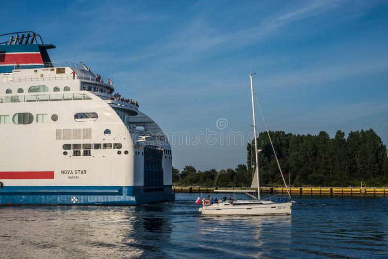 Yacht and stern of big white ferry leaving harbor. Small yacht entering harbor and stern of white ferry ship leaving Gdansk harbor, northern Poland for Sweden royalty free stock images