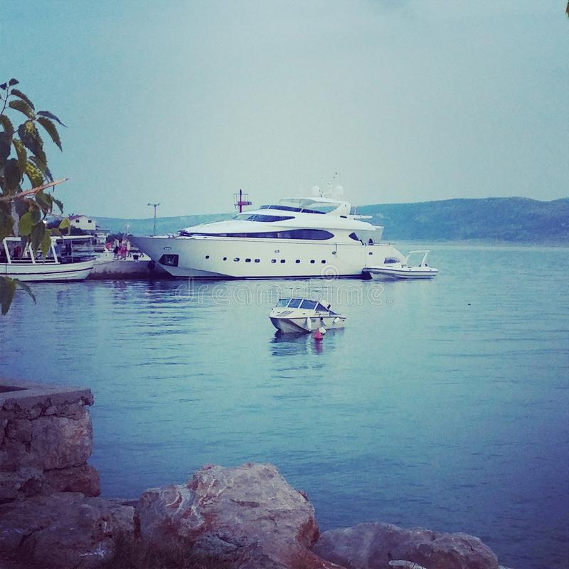 Yacht stupefacente contro una piccola barca fotografia stock