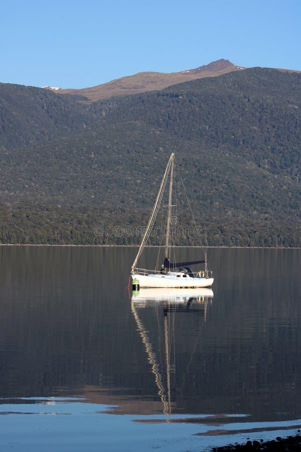 Yacht und Reflexion im See Te Anau, Neuseeland lizenzfreie stockbilder