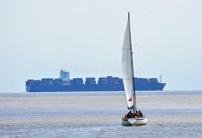 Yacht under Sail with large container ship in the background. royalty free stock images