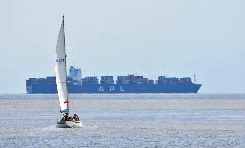Yacht under Sail with large container ship in the background. stock photography