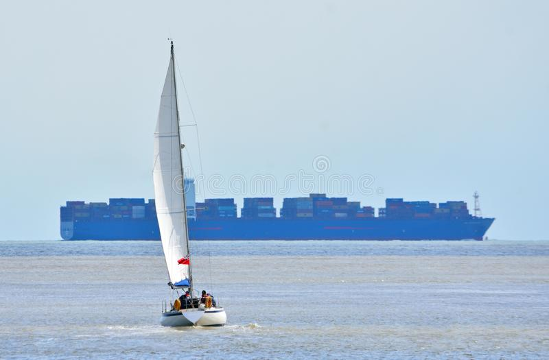 Yacht under Sail with large container ship stock images