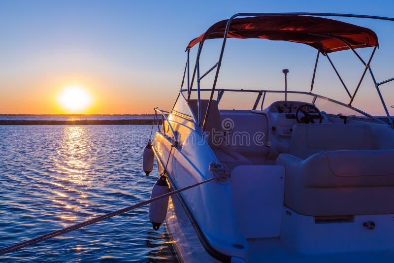 Yacht vicino al pilastro contro il tramonto immagine stock