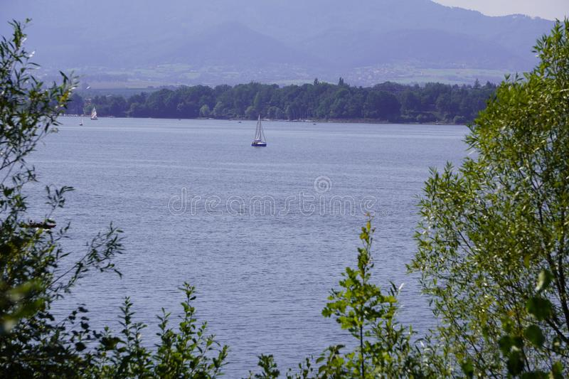 Yacht with a white sail is on the lake against the background of mountains and forests. view from camping, motorhomes, van life. Yacht with white sail is on the stock images