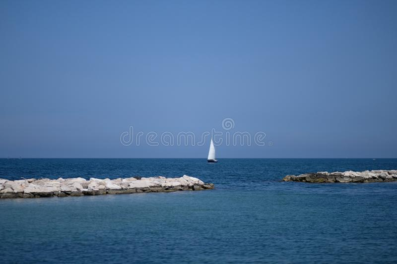 Yacht with a white sail. Against the background of the sea and the blue sky stock image