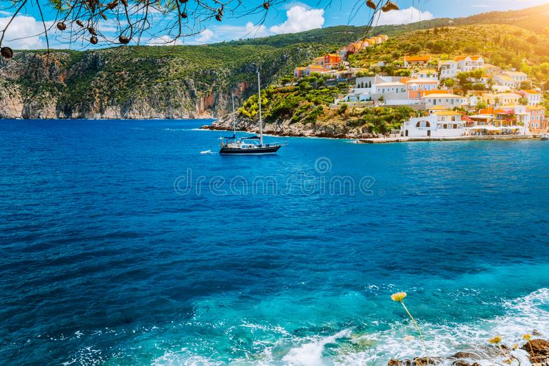Yachten ankom i den härliga Assos byn som lokaliserades på Kefalonia med klart blått havsvatten på tur för sommarsemester omkring royaltyfri bild