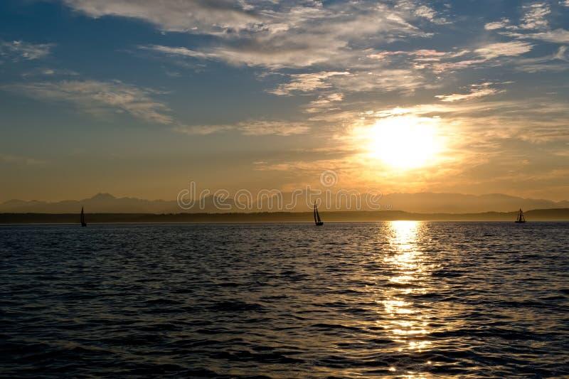 Yachten, die am Sonnenuntergang segeln lizenzfreies stockbild