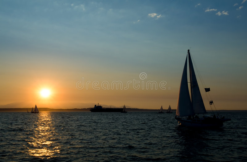 Yachten, die am Sonnenuntergang segeln lizenzfreies stockfoto