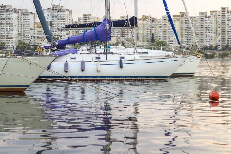 Yachten mit hohen Masten und gesenkte Segel auf dem Hintergrund von städtischen Gebäuden lizenzfreie stockbilder
