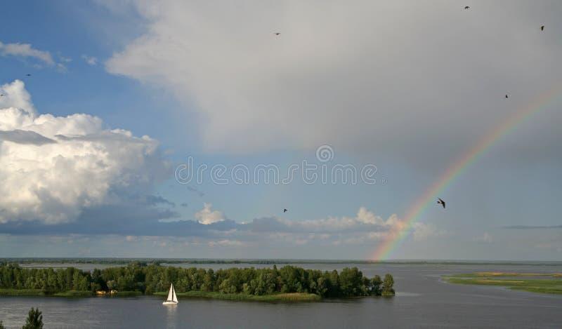 Yachten seglar på flodsikten av en härlig himmel och en regnbåge på bakgrunden royaltyfri fotografi