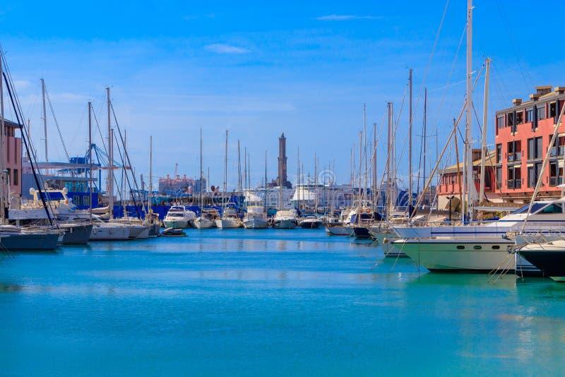 Yachten und Boote im alten Hafen mit einem Leuchtturm in Genua stockfotos