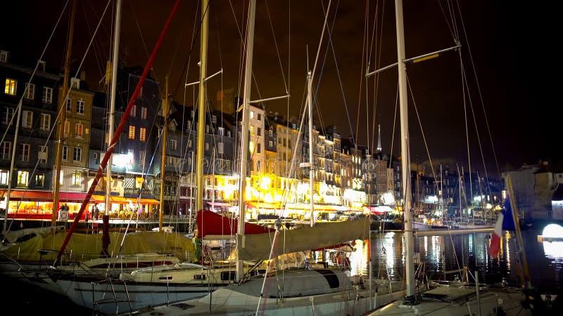 Yachten und Boote machten im Hafen nahe Damm, bunter Stadtabend fest lizenzfreie stockbilder