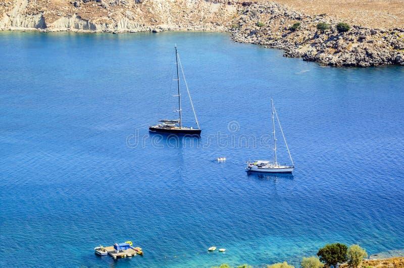 Yachter i Lindos skäller på en ljus solig dag på det blåa vattnet Ön av Rhodes, Grekland royaltyfri fotografi