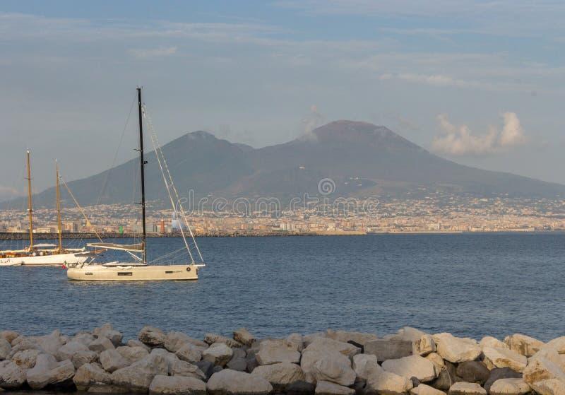 Yachter i skeppsdocka mot den Vesuvius vulkan Fartyg i hamn i Naples Napoli, Italien Segla och loppbegrepp Neapolitan gränsmärke royaltyfri fotografi