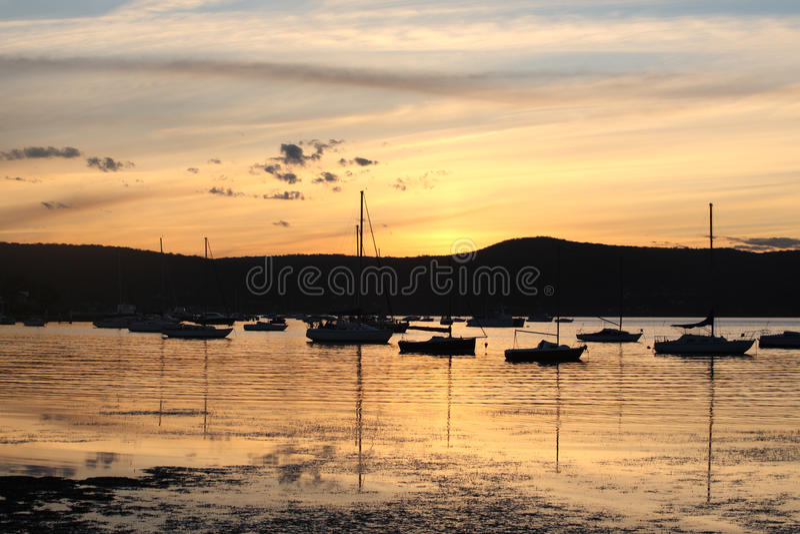 Yachter och fartyg förtöjde på stillsamt vatten på solnedgången royaltyfria bilder