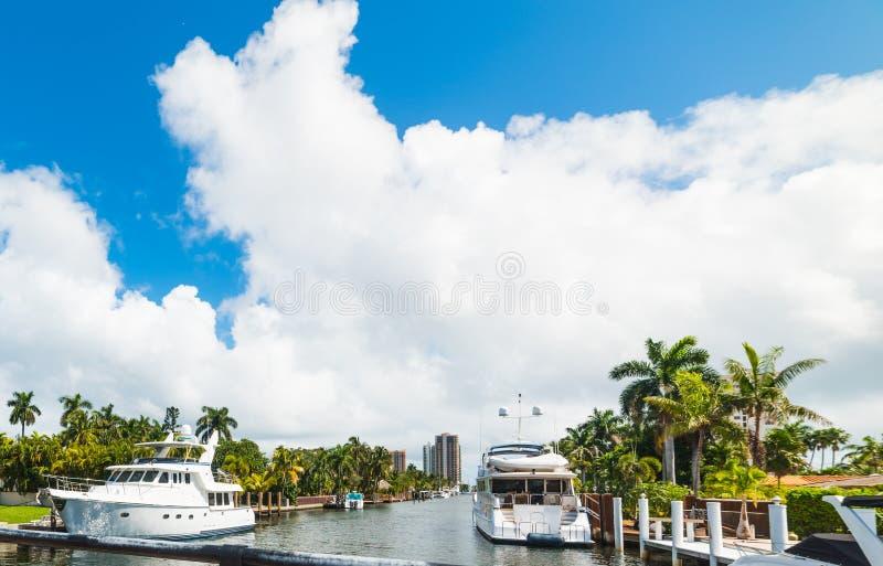 Yachter vid lyxiga hus på en härlig kanal i Fort Lauderdale royaltyfria bilder