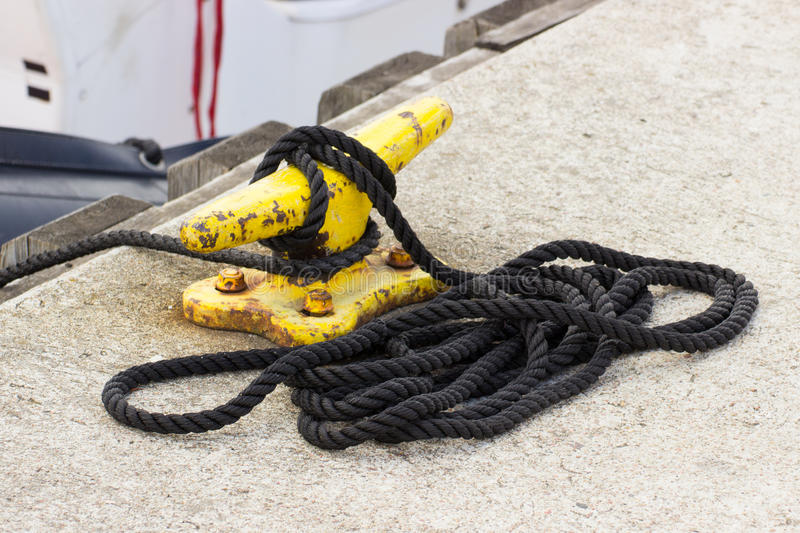 Yachting, black rope and yellow mooring bollard. In port of sailing stock photo