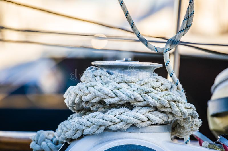Sailboat winch and nautical rope, sailing yacht detail. Yachting, close-up of winch and rope, sailing boat detail view on yacht deck of sailboat royalty free stock photo