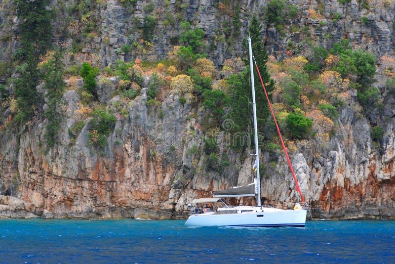 yachting Einsame Yacht steht auf dem Ufer einer malerischen Bucht lizenzfreie stockfotos