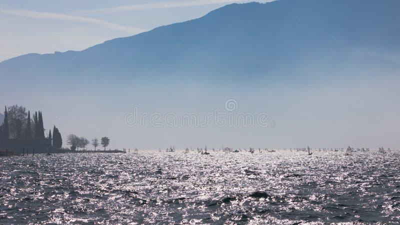 yachting Landschaftspanorama mit Yacht sailer Schiffssegeln durch See oder Meereswellen, wenn Sonnenuntergangsonnensonnenstrahlen stockbild