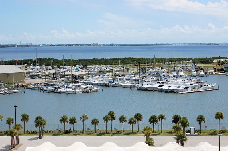 Yachts Marina Florida Palm Trees Tropical. Over looking view of a marina filled with Yachts in Florida with scenic view of the waterway and palm trees stock images