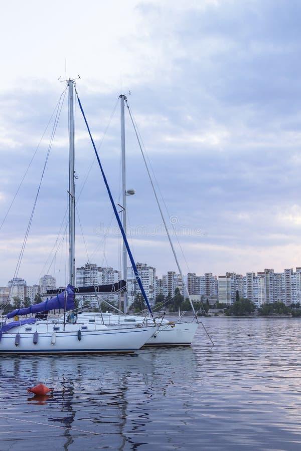 Yachts avec de hauts mâts et voiles abaissées sur le fond des bâtiments urbains images stock