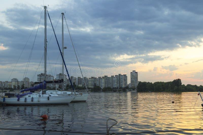 Yachts avec de hauts mâts et voiles abaissées sur le fond des bâtiments urbains Coucher du soleil photos libres de droits