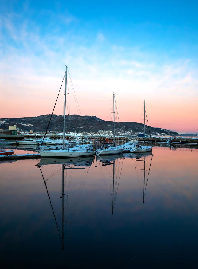 Yachts berthed in the harbor at sunset royalty free stock image