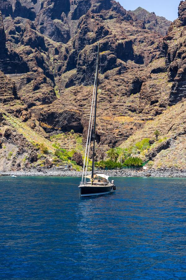 Yachts and boats of tourists near the vertical cliffs Acantilados de Los Gigantes Cliffs of the Giants. stock images