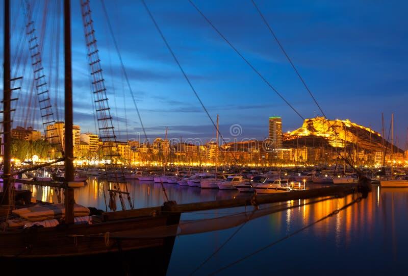 Yachts contre le château dans la nuit Alicante images stock