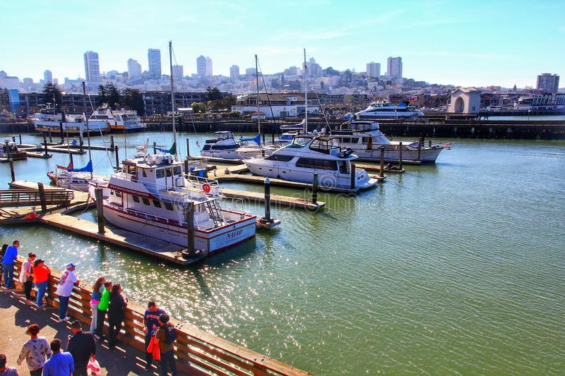 Yachts docked at Pier 39 Marina with city skyline royalty free stock images