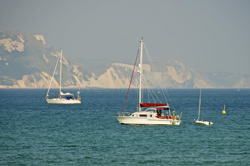Yachts in Dorset. Yachts off the coast of Dorset in England. This area is known as the Jurassic Coast due to the large number of fossils found in the rocks royalty free stock photos