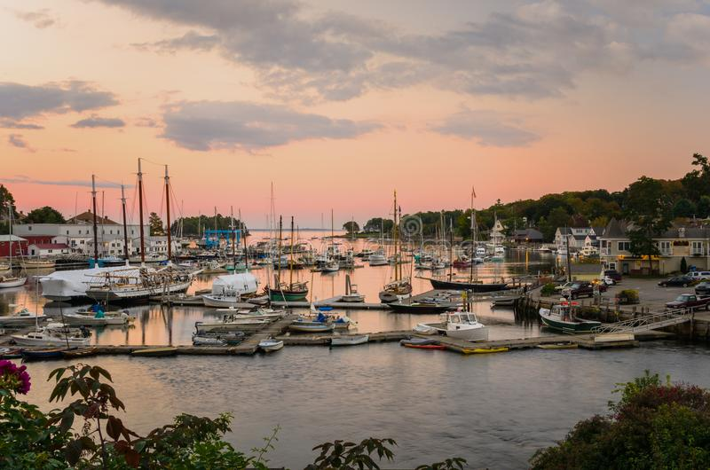 Yachts and Fishing Boats Tied up to Wooden Pier in Harbour. Yarchts and Fishing Boats moored to Wooden Piers in a Beautiful Harbour at Twilight. Camden, ME stock image