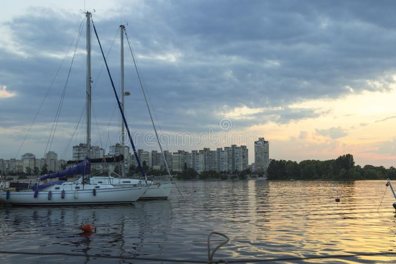 Yachts with high masts and lowered sails on the background of urban buildings. Sunset.  royalty free stock photos