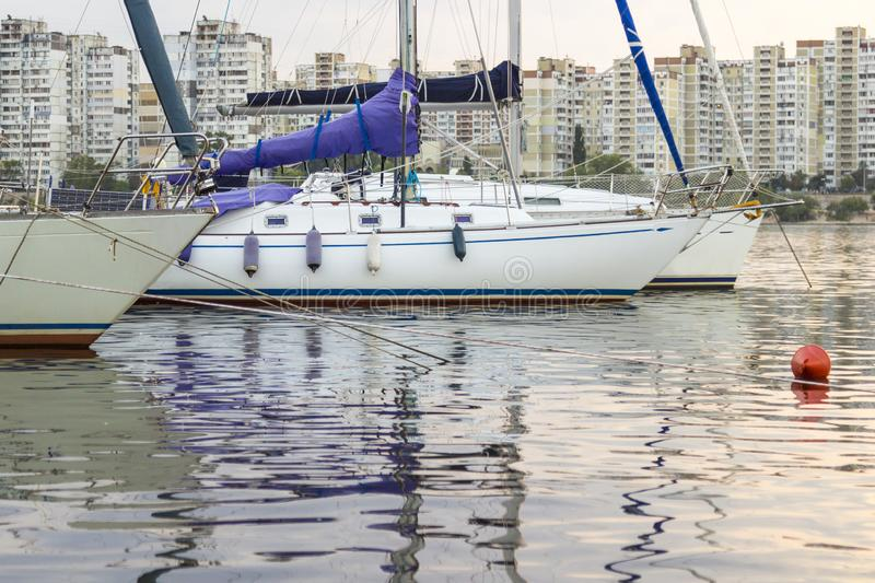 Yachts with high masts and lowered sails on the background of urban buildings.  royalty free stock images