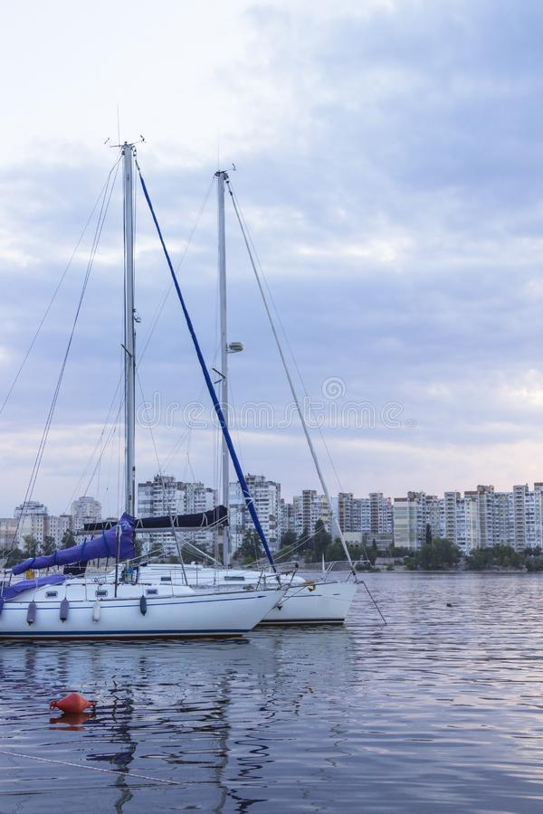 Yachts with high masts and lowered sails on the background of urban buildings.  stock images