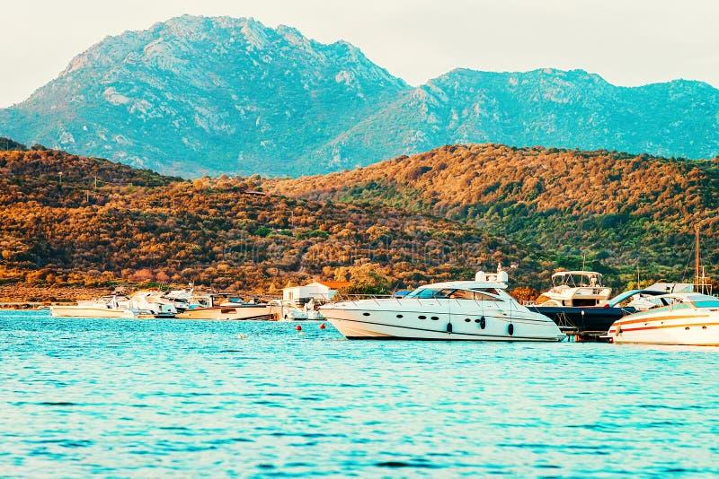 Yachts at the Mediterranean Sea on Costa Smeralda. In Sardinia in Italy at sunrise stock photos