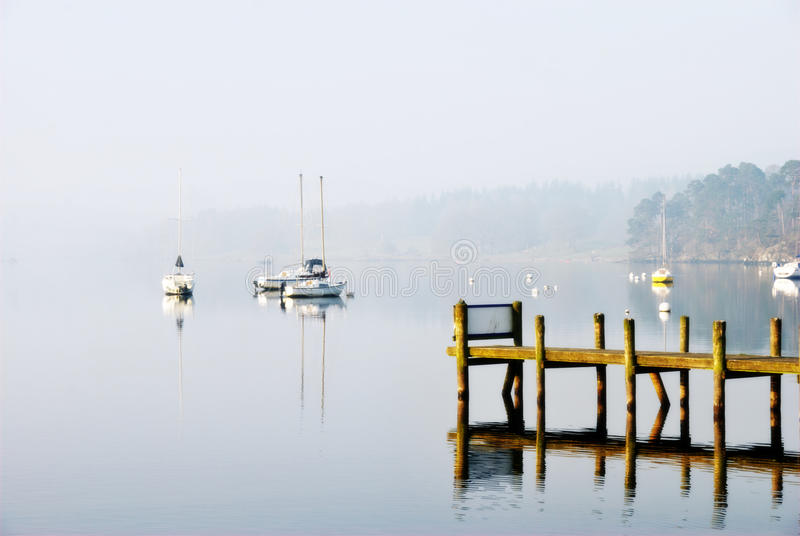 Yachts moored on a misty lake royalty free stock photo