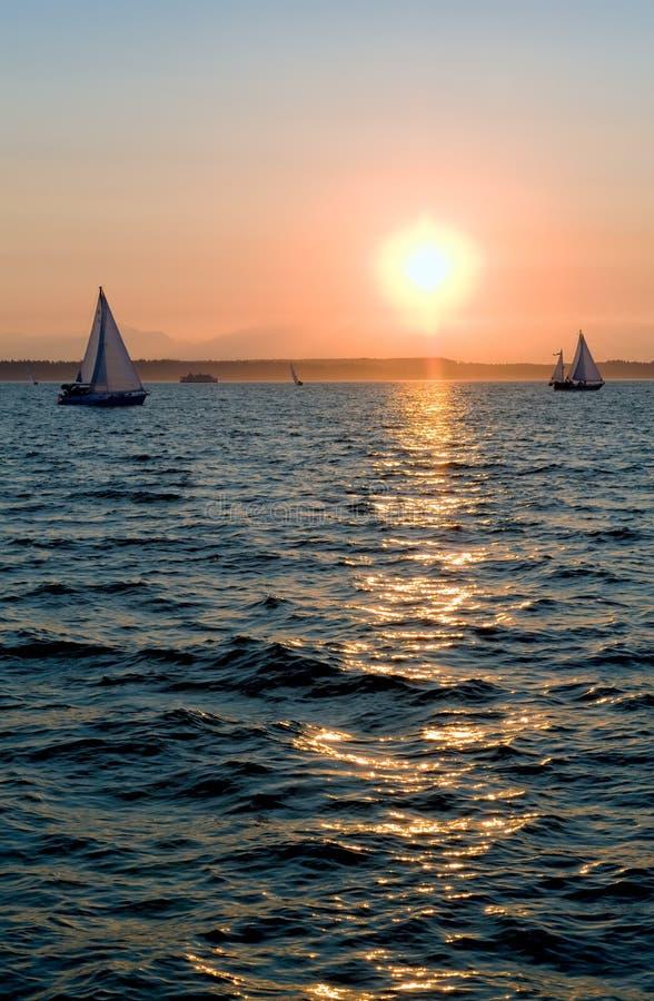 Yachts naviguant au coucher du soleil photos stock
