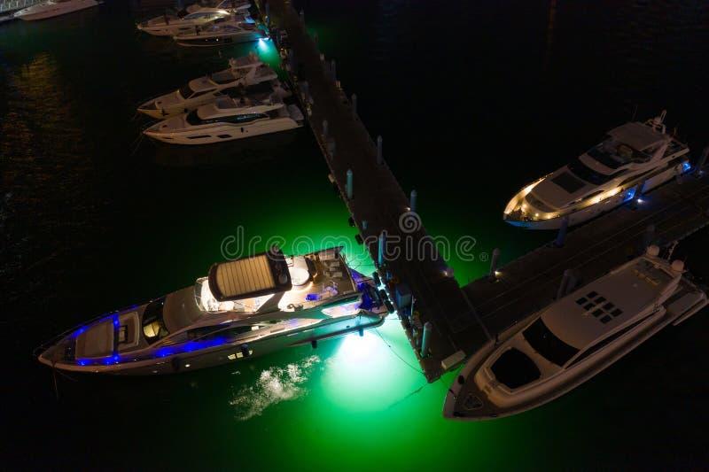 Yachts with neon green underwater lighting Miami aerials stock photo