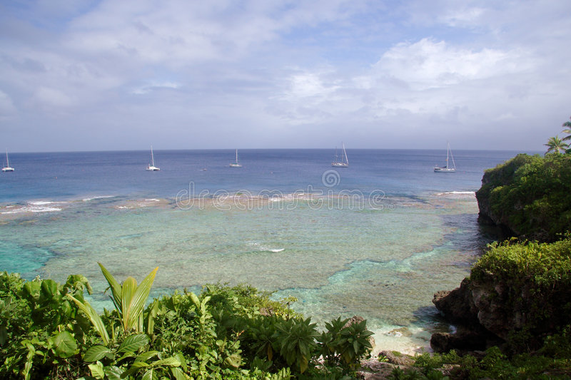 Yachts off tropical island stock image