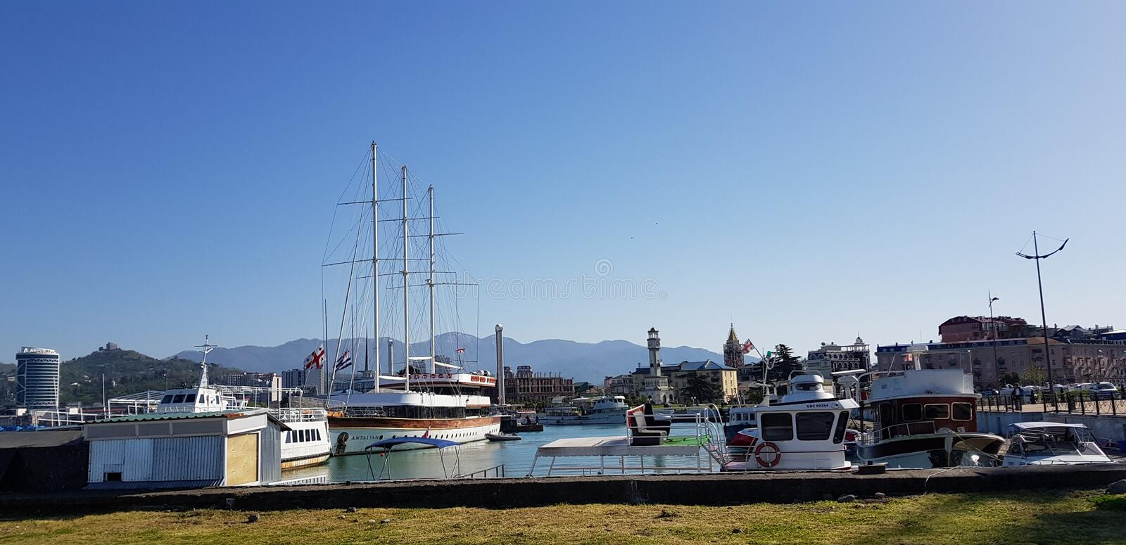 Yachts on the quay in the port. Yachts and other vessels on the quay of Batumi port in anticipation of exit to the Black Sea royalty free stock image
