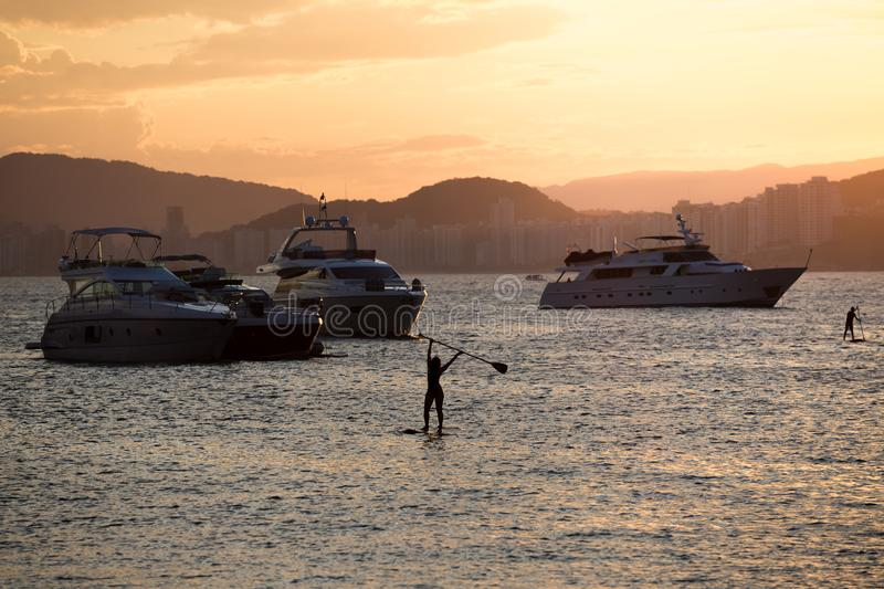 Yachts and people practicing stand up paddle, during the sunset, in Guaruja, Brazil royalty free stock image
