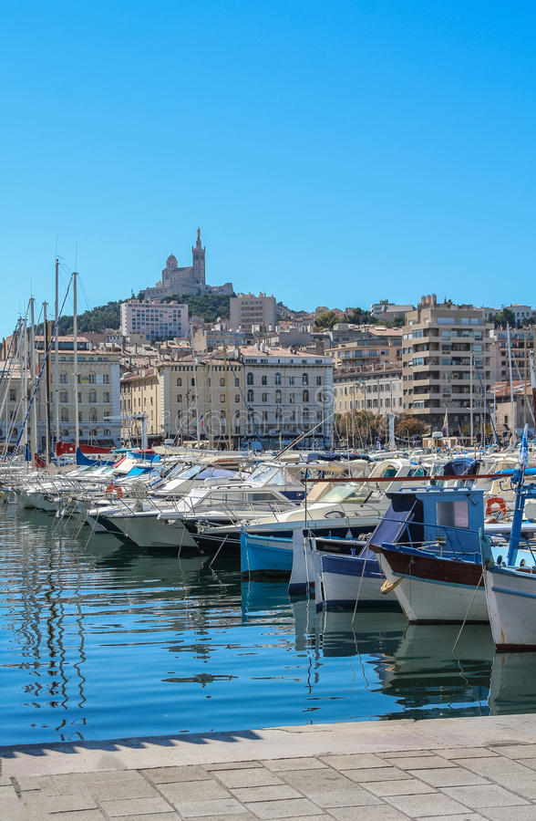 Yachts in the port of Marseilles on the background of the church of Notre Dame de la Garde. On the hill stock photo