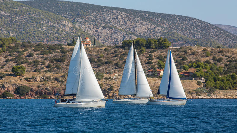 Yachts at Sailing regatta in the wind through the waves at the Sea. Sport. stock photography